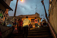 In the hour after sunset, Sri Lankan men and women walk in the center of Kandy. At the top of the stairs a vendor selling produce has a scale attached to his cart.