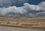 storm clouds drop streams of rain in the distance beyond mesas and power transmission lines along highways US 491/US 160 in northwestern New Mexico near the Colorado state line.  panorama