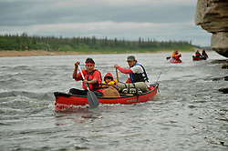 Steve Ellis, back, Hawke Ellis Williams, 4, middle and Dene First Nation youth Tristen Jade Lockhart, 14, paddle down the Thelon river In the middle of the largest and most remote game sanctuary in North America, in the Northwest Territories, just south of the Arctic Circle. Its fate now hangs in the balance, protected on paper, but with little management, no money, and no voice for the Dene, its most ardent advocate for protection, while mining (for diamonds, gold, and uranium) threats, buoyed by recent prices, loom.  Dene youth have rarely been deep into the Thelon, yet the caribou is still their life blood, reverentially important.  These Dene are amongst the last hunter/gatherers in the Northern Hemisphere.   (Photo by Ami vitale)