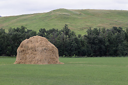 Large haystack piled in the middle of a pasture in Wyoming state.