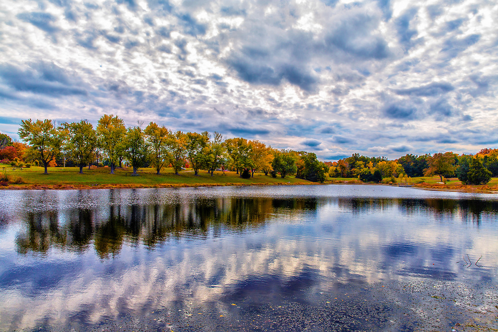 Drama in Autumn Skies Above Broemmelsiek Park Lake in Wentzville, Missouri.<br /> <br /> The trails in this 500+ acre park are in 2 separate sections joined together by restored grassy prairie. They are a mixture of hard packed dirt trails, several small rock gardens, and a few rocky creek crossings.<br /> <br /> The front section is accessed via the concrete bridge that is just off the first parking lot. It's a mixture of wooded single track and open meadows, with several short but steep climbs. Rocky in the beginning, it switches to a dirt base as you start up the ridge.<br /> <br /> The trail then follows the contours of the meadows to the second section, making for a fun, but quick trip to the wooded area in the back of the park. A winding, dirt hillside trail, mixed with rocks leads to a creek crossing, then a rocky ascent as the trail meanders along another ridge line leading to a picturesque view of a local equestrian farm and pond. This section features a wide swooping turn which leads back across the power line alley that divides this part of the trail.