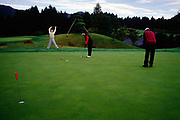A golfer on a golf course limbers up before a shot, Hakone, Japan