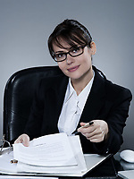 beautiful brunette business woman at her desk proposing signing contract on isolated background