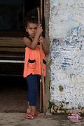 A girl holds  a snooker cue, in Jardim São Marcos favela, Cubatão