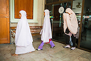 "11 JANUARY 2013 - BANGKOK, THAILAND:   Girls from a neighborhood Muslim school walk into a Mosque for noon prayers in the Ban Krua neighborhood in Bangkok. The Ban Krua neighborhood of Bangkok is the oldest Muslim community in Bangkok. Ban Krua was originally settled by Cham Muslims from Cambodia and Vietnam who fought on the side of the Thai King Rama I. They were given a royal grant of land east of what was then the Thai capitol at the end of the 18th century in return for their military service. The Cham Muslims were originally weavers and what is known as ""Thai Silk"" was developed by the people in Ban Krua. Several families in the neighborhood still weave in their homes.       PHOTO BY JACK KURTZ"