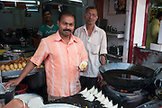 Street vendor prepares and sells Samosa off a street stall. Photographed in Cochin, India