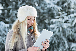 Teenage girl using digital tablet and smiling in winter, Bavaria, Germany