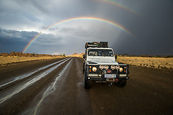 March 3, 2015 - Keetmanshoop, South Africa - Keetmanshoop, Namibia, Africa - Land Rover driving down wet road with rainbow arching in the sky behind it (Credit Image: © Edwin Remsberg/VW Pics via ZUMA Wire)