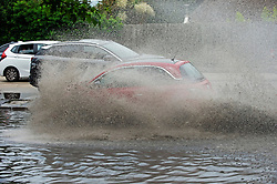 © Licensed to London News Pictures 17/06/2021. Aylesford, UK. Heavy flooding to the A20 London road in Aylesford, Kent, near Maidstone as this little red car hits the water fast. Torrential rain brings flooding to Kent roads with more expected in the coming days as the heatwave ends. Photo credit:Grant Falvey/LNP