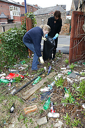 Young people picking up discarded cans; bottles and other rubbish in the community,