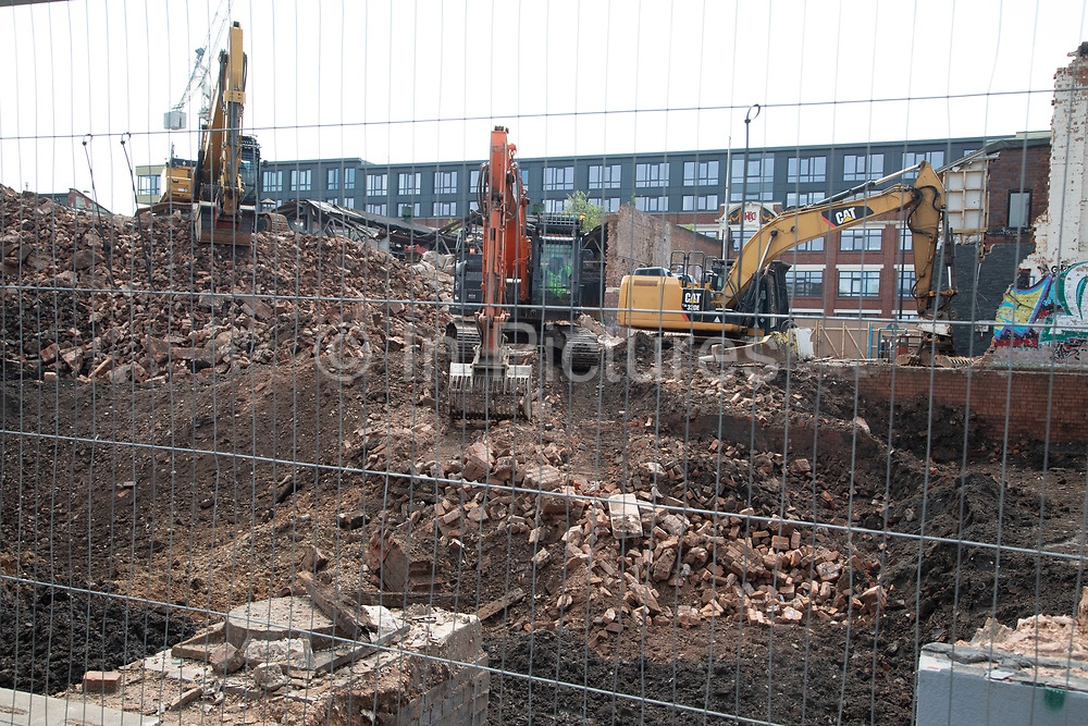 Redevelopment taking place in Digbeth in Birmingham, United Kingdom. Diggers ar on site clearing old industrial buildings in preparation for new developments.