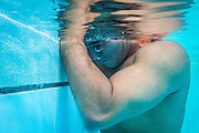 """2016/06/04 – Bogotá, Colombia: Moises Fuentes Garcia, 41, takes a break during a training session at the Simon Bolivar Aquatic Complex, Bogotá, 4th June, 2016.<br />  -<br /> Moises used to be a farmer and sell cattle with his brother when in October 1992, Paramilitaries in the region of Santa Marta targeted them. Moises was shot six times, and his brother killed. He was """"lucky"""" to survive, one of the bullets crossed his neck, and one stuck into his spine and he couldn't walk again. However it did not end there, a few months later, during a rehabilitation session he broke his leg and due to an infection he had to amputate it. Moises felt it wasn't worth living anymore. But after meeting a group of other victims that had even more severe injures, he grabbed life with will and began to feel motivated. He started playing wheelchair basketball and studying. In the process of the rehabilitation he was spotted as a good swimmer, even if he didn't possess any technique. After some success on the swimming pool, he became completely dedicated to the sport, while finishing degrees as a tailor, public accountant and hopes to graduate as a sport teacher next year. <br /> Among many achievements he won the Bronze medal in 2008 Paralympic Games in Beijing and Silver medal on the 2012 Paralympic Games in London on the 100 meters breaststroke category. He also became the World Champion at the 2013 World Swimming Championships. Moises hopes that in the Rio 2016 Paralympics, he will bring gold home. <br /> He believes that people must value their life, what they have and help people on the way. """"Everyone is a champion, but some people don't do the necessary to really became one"""" he says. (Eduardo Leal)"""