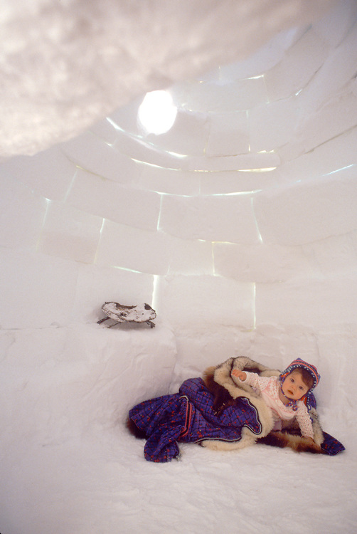 Alaska. Barrow. A small native child wrapped in warm furs inside of an igloo.
