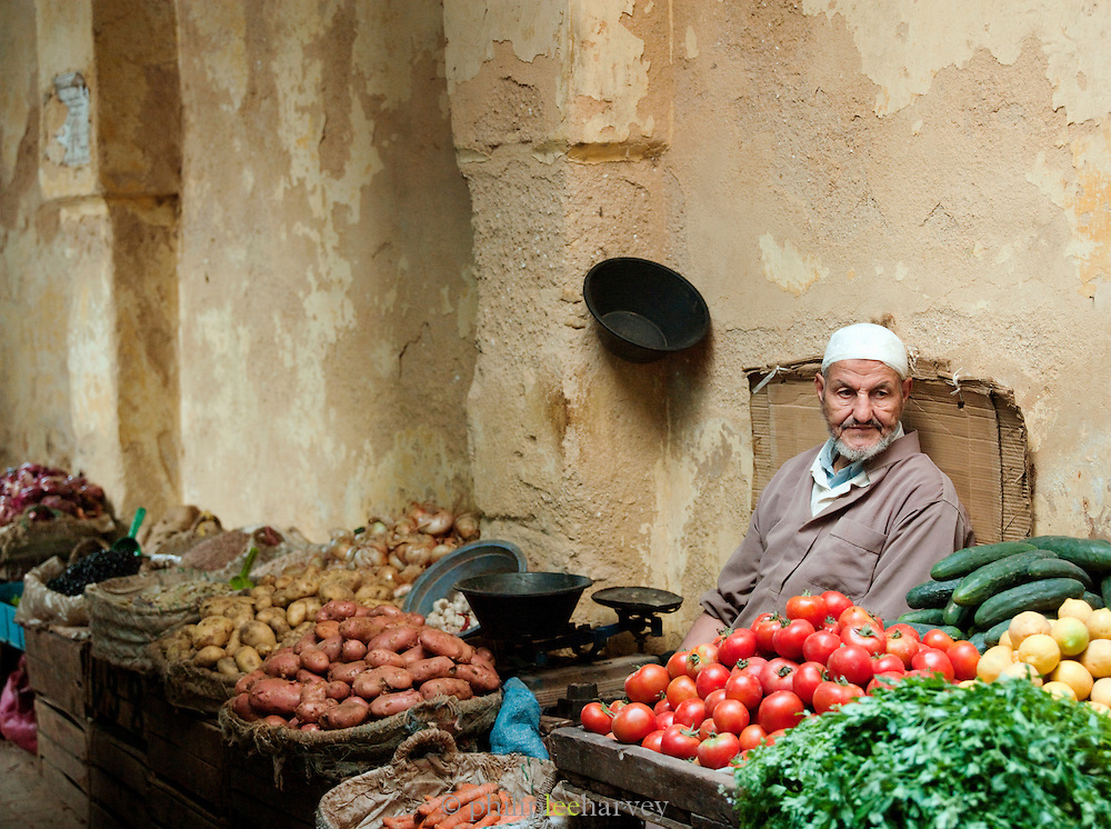 A fruit and vegetable stall and seller in the narrow streets of the medina, Fes, Morocco