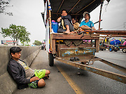 21 FEBRUARY 2014 - KHLONG CHIK, PHRA NAKHON SI AYUTTHAYA, THAILAND: A Thai farmer relaxes on the highway south of Ayutthaya. About 10,000 Thai rice farmers, traveling in nearly 1,000 tractors and farm vehicles, blocked Highway 32 near Bang Pa In in Phra Nakhon Si Ayutthaya province. The farmers were traveling to the airport in Bangkok to protest against the government because they haven't been paid for rice the government bought from them last year. The farmers turned around and went home after they met with government officials who promised to pay the farmers next week. This is the latest blow to the government of Yingluck Shinawatra which is confronting protests led by anti-government groups, legal challenges from the anti-corruption commission and expanding protests from farmers who haven't been paid for rice the government bought.    PHOTO BY JACK KURTZ