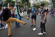 Group of lads have fun playing football with a coconut. The 50th Notting Hill Carnival in West London. A celebration of West Indian / Caribbean culture and Europe's largest street party, festival and parade. Revellers come in their hundreds of thousands to have fun, dance, drink and let go in the brilliant atmosphere. It is led by members of the West Indian / Caribbrean community, particularly the Trinidadian and Tobagonian British population, many of whom have lived in the area since the 1950s. The carnival has attracted up to 2 million people in the past and centres around a parade of floats, dancers and sound systems.