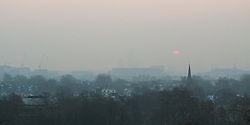 The sun and the city is partially obscured by mist as it rises, viewed from Primrose Hill in Camden. Primrose Hill, London, February 21 2018.