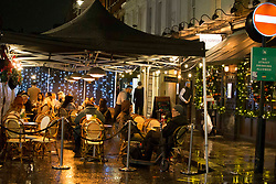 © Licensed to London News Pictures.14/12/2020. London, UK. Despite the rainy weather Londoners are seen enjoying themselves in Soho, before London will go into Tier 3 on Wednesday. Photo credit: Marcin Nowak/LNP