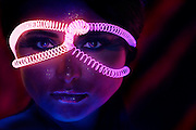 Portrait of a pretty woman with glowing coils wrapped around face.Black light