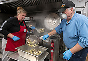 HYANNIS - Faith Family Kitchen chef Jeni Wheeler and volunteer Jack Joyce pull clams from the cauldron on Friday, April 3, 2020. A donation from SPAT featured Holbrook littlenecks over butter garlic pasta.