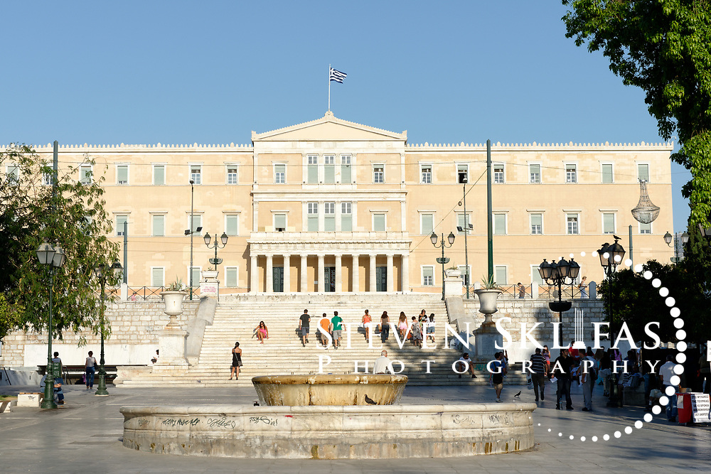 Syntagma square. Athens. Greece. View of the neoclassical façade of the Greek Parliament building opposite Syntagma Square in Athens. The building also known as Vouli was erected in 1836-42 and was originally the Royal Palace. Below the building is the monument to the Unknown Soldier, erected in 1929-1932, it depicts a relief of a dying Greek solider modelled on a figure from the pediment of the Temple of Aphaia at Aegina.  The monument is guarded around the clock by two elite members of the Presidential ceremonial guard unit known as Evzones.