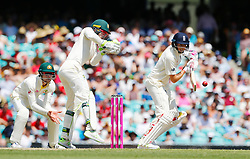 England's Joe Root plays a shot as Tim Paine looks on during day four of the Ashes Test match at Sydney Cricket Ground.