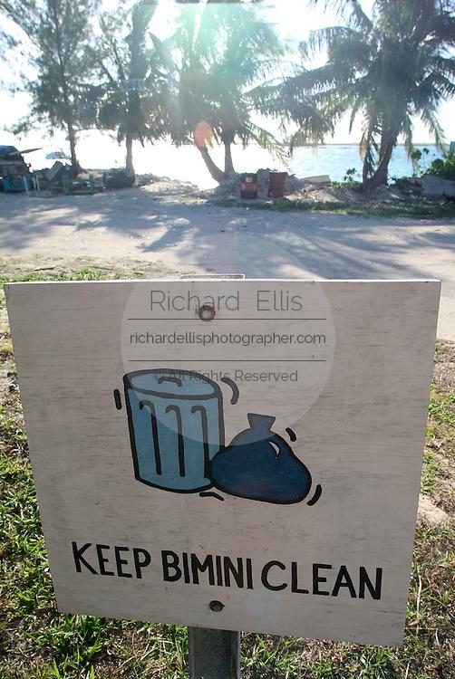 A hand-painted Keep Bimini Clean sign along a palm line street in the tiny Caribbean island of Bimini, Bahamas