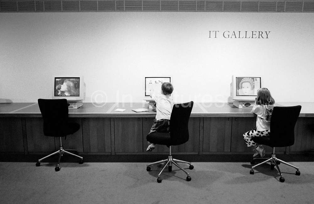 """Two children play on interactive computers in an upper floor of the National Portrait Gallery, the well-known art museum on Trafalgar Square in Central London. The institution's IT Gallery allows young users to search and discover for themselves great works of art from its extensive database including this image of the Tudor Queen Elizabeth I whose painted portraits are on view elsewhere: Her face seen on the far right screen. From a personal documentary project entitled """"Next of Kin"""" about the photographer's two children's early years spent in parallel universes. Model released."""