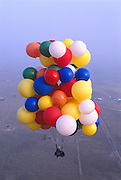 Cluster balloonist, John Ninomiya's balloons are not all directly tied to Ninomiya's harness. He has devised a system of eight color-coded webbing straps of differing lengths that lead to caribiners connecting the twine. That way, the balloons are neatly arranged above him in tiers enabling a safe and certain release.