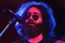 Jerry Garcia looking out over the Audience in Contemplation. The Grateful Dead in Concert at the Huntington Civic Center, Huntington West Virginia on 16 April 1978. A tight headshot of Jerry up to the mic but not singing. Image No. 78C03-33