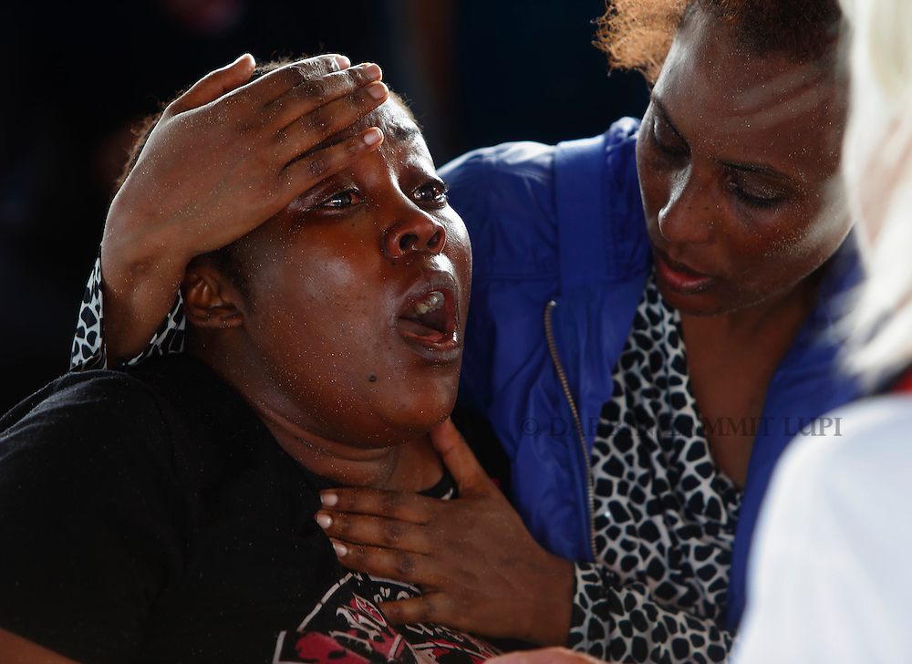 Migrants react after boarding the Migrant Offshore Aid Station (MOAS) ship MV Phoenix some 20 miles (32 kilometres) off the coast of Libya, August 3, 2015.  118 migrants were rescued from a rubber dinghy off Libya on Monday morning . The Phoenix, manned by personnel from international non-governmental organisations Medecins san Frontiere (MSF) and MOAS, is the first privately funded vessel to operate in the Mediterranean.<br /> REUTERS/Darrin Zammit Lupi <br /> MALTA OUT. NO COMMERCIAL OR EDITORIAL SALES IN MALTA