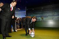11 APR 2005 HANNOVER/GERMANY:<br /> Utz Claassen (L), Vorstandsvorsitzender EnBW, und Gerhard Schroeder (S), SPD, Bundeskanzler, der an einem Simulator fuer Elfmeterschiessen Fussball spielt, am Messestand von Energie Baden-Wuerttemberg, EnBW, Hannover Messe<br /> IMAGE: 20050411-01-020<br /> KEYWORDS: Gerhard Schröder