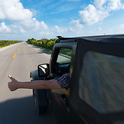 Thumb Up From the Window Of Jeep On Empty Seaside Road, Cozumel, Mexico