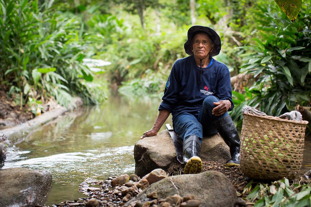 Estefania Cotera takes a break by the stream that snakes through her property.