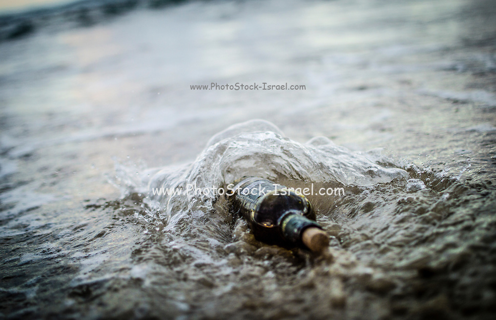 Message in a bottle - a bottle half buried in sand on a beach