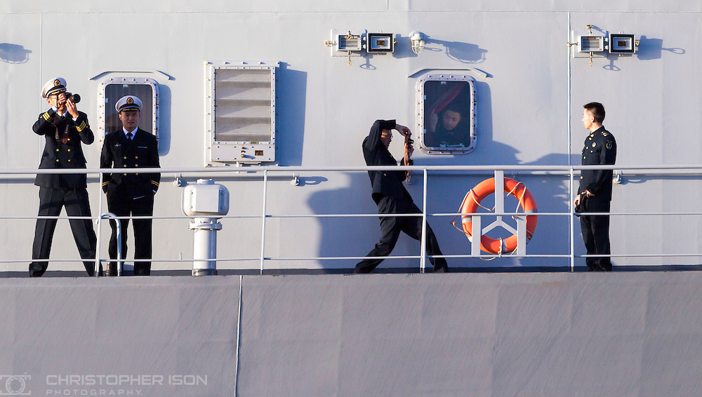 Officers aboard the Chinese Naval replenishment ship Chaohu take photos as they enter Portsmouth harbour today. The ship is involved in the first visit by the Chinese Navy to the UK since 2007. She is accompanied by the frigate Yun Cheng and the assault ship Chang Bai Shan. They arrived in Portsmouth 24 hours early due to the expected bad weather. The Royal Navy statement stated that the five day formal visit is aimed at enhancing military understanding between the UK and China. Picture date Sunday 11th January, 2015.<br /> Picture by Christopher Ison. Contact +447544 044177 chris@christopherison.com