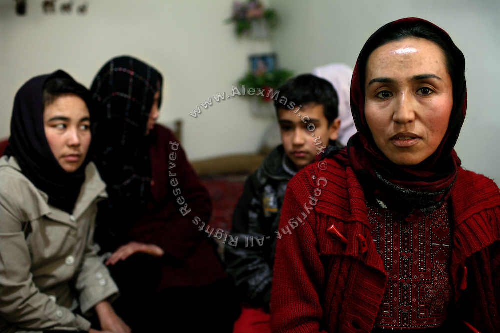 Aghele Rezaie, 30, (right) the famous Afghan actress who has taken part in the controversial movie 'At Five in the Afternoon' (Winner of the Cannes Film Festival Jury Prize in 2003) is portrayed while sitting in her home with her family in Kabul, Afghanistan. 'At Five in the Afternoon' focuses on the life of a progressive young woman who dreams of growing up to become the President of the Republic despite her oppressive home life and a strained relationship with her bigoted but loving father. The film follows the daily struggles of Afghan women in post-Taliban Afghanistan with tenderness and hope against a tragic background of death and despair.