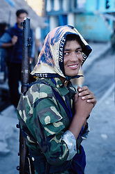 Kusapani, 03 March 2005... A Maoist soldier wearing a 'Titanic's scarf'. The so called People's Army or Red Army have just arrived in the small village of Surket District. They will get some food and spend the night here. Their uniform is identical to the one used by the RNA. They claim that they steal the weapons from the Armed Police Force and/or from the Royal Nepal Army. They also get weapons from the black market in india. About two years ago a Nepalese newspaper has published a photo of Maoists buying weapons in India.