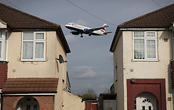 """© Licensed to London News Pictures. 27/10/2016. London, UK. A British Airways airliner is glimpsed between houses near Heathrow Airport as it lands. The government has announced that a third runway will be built at the United Kingdom's busiest airport. The Cabinet are divided - with Foreign Secretary Boris Johnson saying that the project is """"undeliverable"""". Conservative MP for Richmond Zac Goldsmith has resigned. Photo credit: Peter Macdiarmid/LNP"""