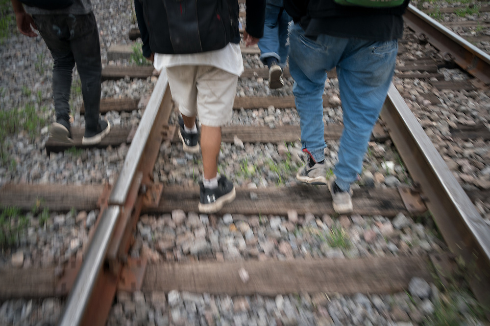A group of migrant workers in Apizalco, Mexico walk along railway tracks as they wait for a train heading north to the US.