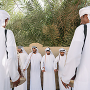 Men doing the Al Ayala dance. It is a traditional group dance of United Arab Emirates. The dance is accompanied with traditional music, and a separate group of male and female are represented.