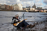 A walk along the River Thames on the Southbank in London. A busker called the 'Flame Proof Moth' performs on the edge of the River Thames with St Paul's Cathedral as a backdrop. Playing an electric guitar and singing amusing poetry like songs, busking has never been so creative.  This area is very popular especially on the weekends for Londoners to walk and see different arts, culture and entertainment.
