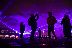 © Licensed to London News Pictures. 17/01/2018. London, UK. Visitors walk through a laser and smoke light show entitled 'Waterlicht' by Daan Roosegaarde as it fills the night sky above Granary Square in King's Cross during the Lumiere London festival. Running from 18th-21st January 2018 more than 50 artworks? are transforming the capital's streets, buildings and public spaces into an immersive nocturnal art exhibition of light and sound. Locations include King's Cross, Fitzrovia, Mayfair, West End, Trafalgar Square, Westminster, Victoria, South Bank and Waterloo. Photo credit: Peter Macdiarmid/LNP