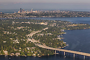Interstate 90 crosses Lake Washington and Mercer Island in this aerial view over Bellevue, Washington. The Seattle skyline and Mount Constitution, part of the Olympic Mountains, is visible in the background.