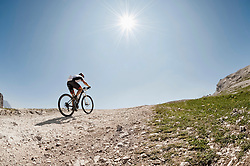 Mountainbiker riding up steep mountain track