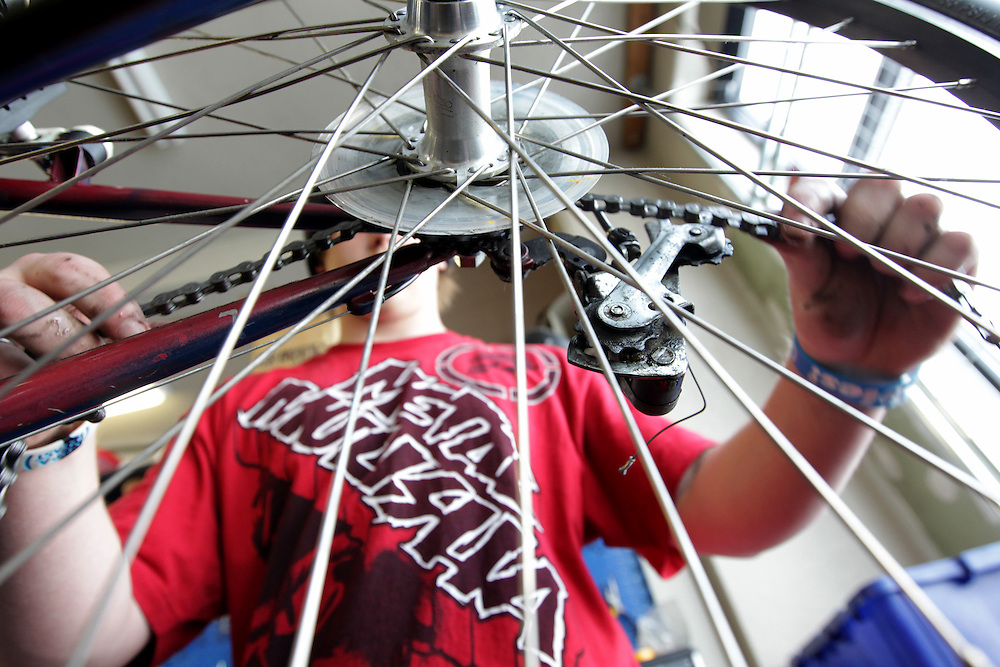 Ty Spangle, 17, replaces a chain on a refurbished bicycle at Express Bike Shop in St. Paul, Minnesota.  Formerly a Youth Express apprentice, Spangle is now a mechanic at the shop, teaching skills to new program participants...