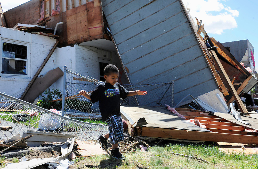 A boy walks through the yard of a home damaged by a tornado a day before in Springfield, Mass., Thursday, June 2, 2011.   Residents of 19 communities in central and western Massachusetts woke to widespread damage Thursday, a day after at least two late-afternoon tornadoes shocked emergency officials with their suddenness and violence and caused the state's first tornado-related deaths in 16 years.  (AP Photo/Jessica Hill)