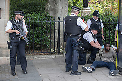 © Licensed to London News Pictures. 22/06/2017. London, UK. Armed police (L) stand on guard as colleagues search a man on the ground they are detaining who earlier was tasered near an entrance to Parliament. Photo credit: Peter Macdiarmid/LNP