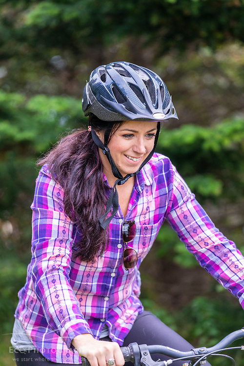 A woman rides a bike at Quoddy Head State Park in Lubec, Maine.