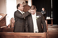 Best man adjusting groom's collar before wedding ceremony